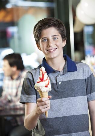 parlor: Portrait of happy boy showing vanilla ice cream at parlor