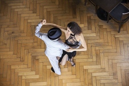 High angle view of male and female dancers performing on hardwood floor at restaurant