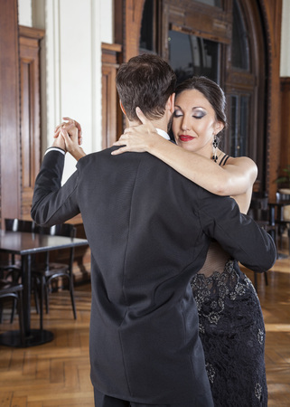 closing: Romantic mid adult woman closing eyes while performing tango with man in restaurant