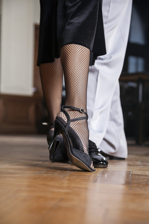 Low section of male and female tango dancers performing in restaurant