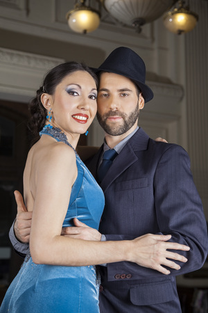 argentina dance: Portrait of confident male and female tango dancers embracing in restaurant