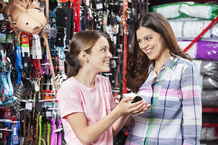 pet store: Happy mother and daughter with guinea pig in pet store Stock Photo