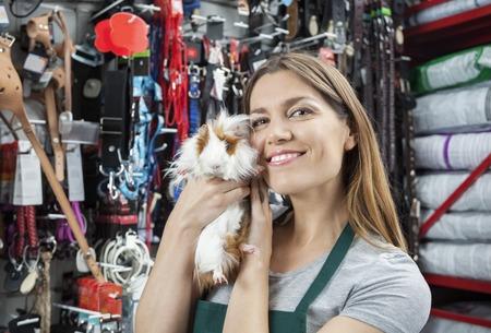 petshop: Portrait of beautiful saleswoman holding cute guinea pig at store Stock Photo