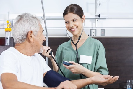 long term care services: Smiling female nurse checking blood pressure of senior male patient in rehab center