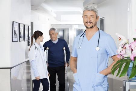 Portret van vertrouwen arts staan met de handen in de zakken, terwijl collega en senior patiënt in achtergrond communiceren op revalidatiecentrum
