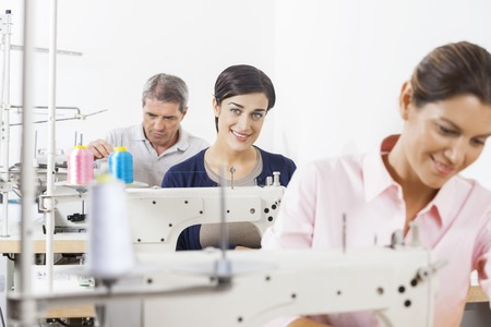 modiste: Portrait of happy female tailor with colleagues working in sewing factory Stock Photo