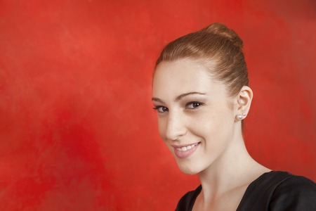 20s  closeup: Closeup portrait of young female ballet dancer smiling against red wall in studio
