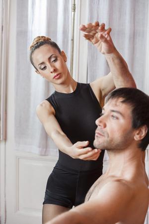 ballet hombres: entrenadora ayudar a bailarina de ballet masculino en la sala de ensayo