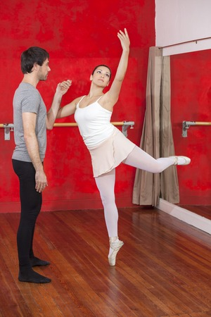 mid adult male: Mid adult male trainer holding ballerinas hand as she performs in studio Stock Photo