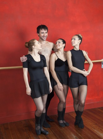 Smiling mid adult trainer standing arms around female ballet dancers in studio