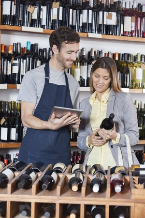 store keeper: Smiling salesman using digital tablet while female customer holding wine bottle in shop