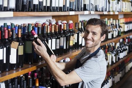 shop keeper: Portrait of smiling salesman arranging wine bottle on shelf in shop