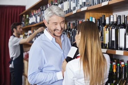 shop keeper: Happy mature customer looking at saleswoman showing wine bottle in shop Stock Photo