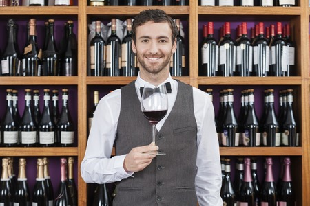 selling service smile: Portrait of confident bartender holding red wine glass against shelves in winery