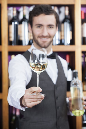 store keeper: Portrait of confident bartender offering white wine glass against shelves in winery