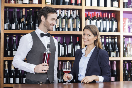 store keeper: Smiling female customer and bartender with red wine at counter in shop