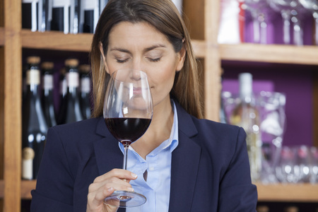 smelling: Mid adult female customer smelling red wine in shop