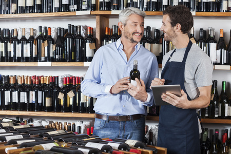 store keeper: Smiling salesman using digital tablet while male customer holding wine bottle in shop Stock Photo