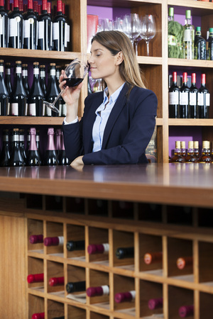 mid adult   female: Mid adult female customer smelling red wine against shelves in winery