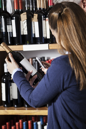 scanning: Couple scanning barcode on wine bottle through smartphone in supermarket Stock Photo