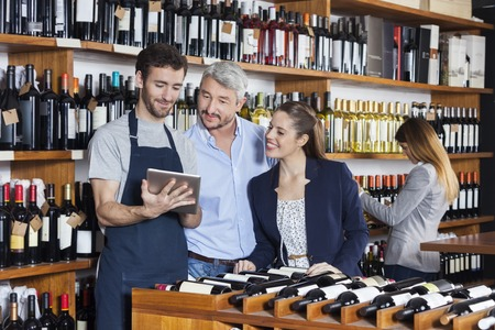 Smiling young salesman showing wine information to customers on tablet computer in shop