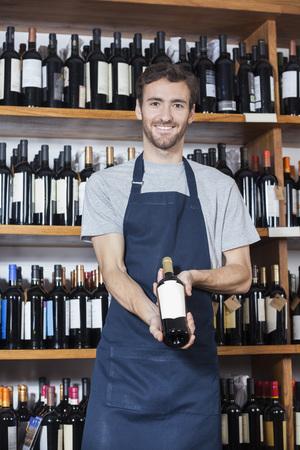 store keeper: Portrait of confident salesman showing wine bottle in shop