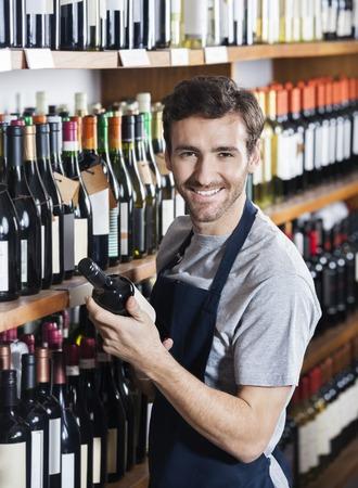 store keeper: Portrait of confident salesman arranging wine bottle on shelf in shop