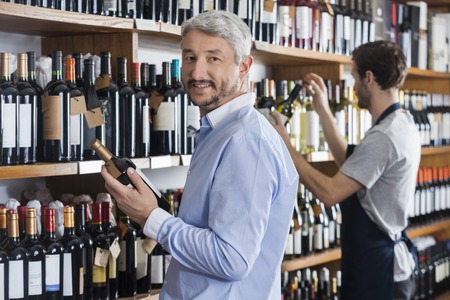 store keeper: Portrait of mature customer holding wine bottle while salesman working in shop