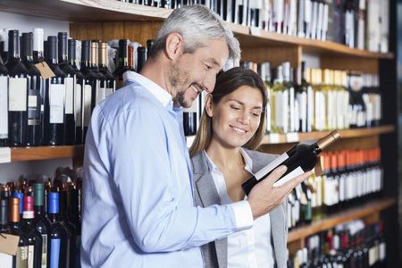 liquors: Smiling couple looking at wine bottles label in shop
