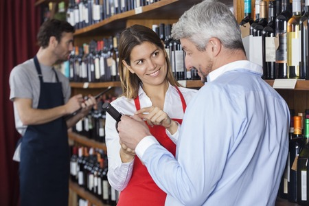 shop keeper: Smiling saleswoman showing wine bottle to customer while colleague working in background at shop
