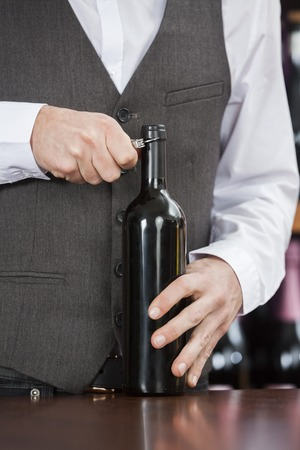 store keeper: Midsection of bartender opening wine bottle at table in winery Stock Photo