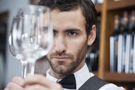 store keeper: Closeup of young bartender examining wineglass at winery Stock Photo