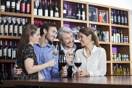 shop keeper: Happy male and female friends enjoying wine at counter in winery