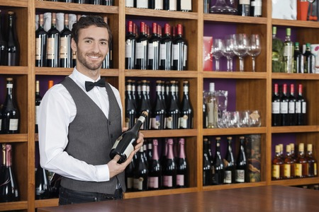 store keeper: Portrait of confident young bartender holding red wine bottle at counter in shop
