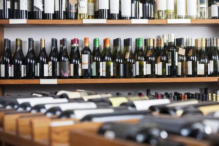 store keeper: Wine bottles displayed on shelves in supermarket