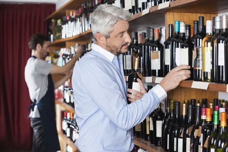 store keeper: Mature male customer choosing wine bottle while salesman working in shop