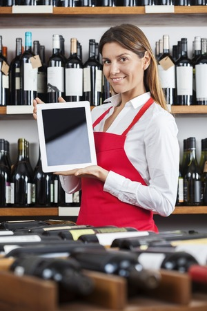 store keeper: Portrait of smiling saleswoman showing blank tablet computer in winery