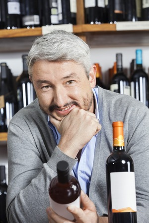 store keeper: Portrait of happy mature man with hand on chin holding wine bottle in shop Stock Photo