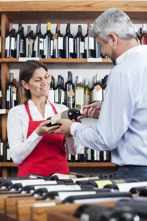 shop keeper: Mid adult saleswoman giving wine bottle to male customer in shop