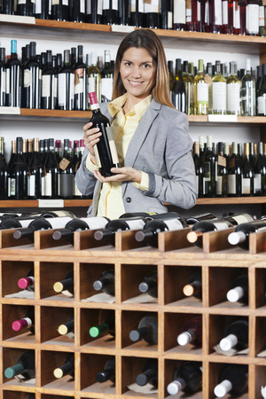 mid adult   female: Portrait of mid adult female customer holding wine bottle at rack in shop