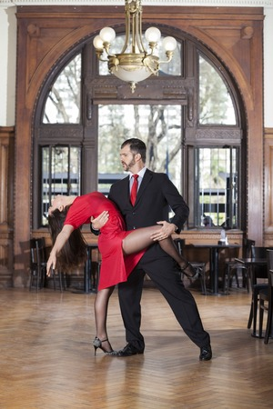 show window: Full length of professional tango dancers performing in restaurant