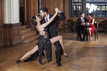 legs open: Confident tango dancers performing open legs step while couple dating in restaurant