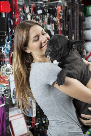 petshop: Loving mid adult woman carrying French Bulldog in store