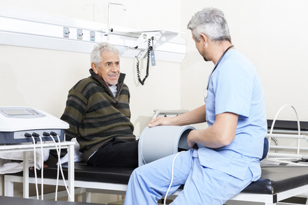 Smiling senior patient looking at doctor receiving relectromagnetic therapy