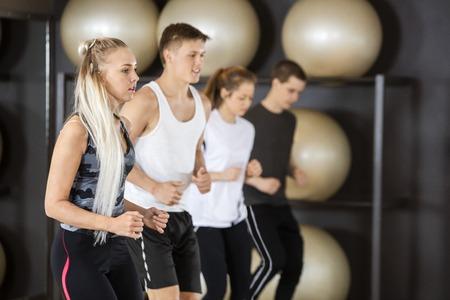 fitness hombres: Mujer joven del ajuste que ejercita con los amigos en el gimnasio