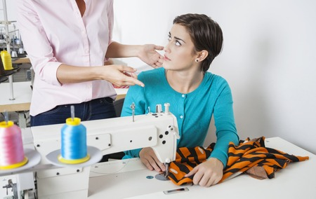 designer at work: Midsection of angry tailor gesturing at employee working in sewing factory
