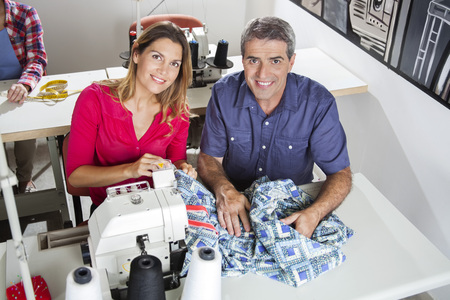 High angle portrait of confident tailors sitting at workbench in sewing factory Stock Photo
