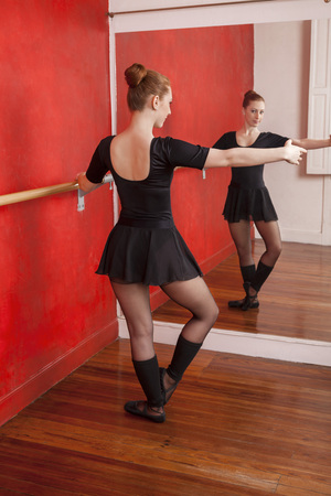 full length mirror: Full length of young female ballet dancer practicing in front of mirror at studio