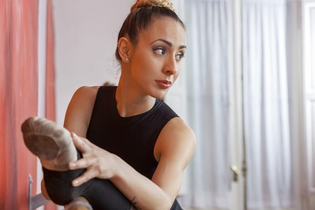 barre: Young ballerina stretching her leg while looking away in dance studio Stock Photo