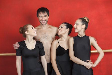 ballet hombres: Happy bailarinas de ballet mirando profesor de sexo masculino en el estudio Foto de archivo